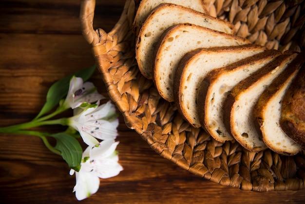 Op een houten tafel in een mand zijn plakjes gesneden witbrood van de bovenkant verwijderd