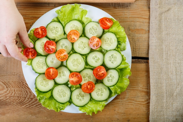 Op een houten tafel legt een vrouw de kerstomaatjes op een bord met komkommers.