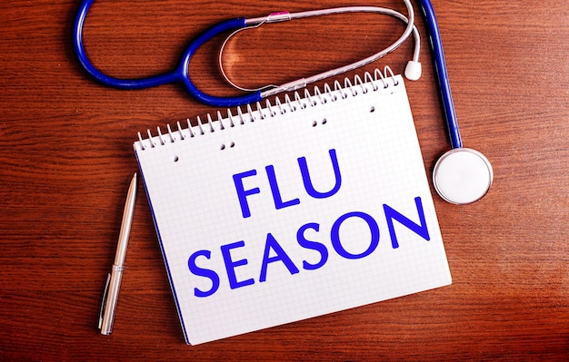 Op een houten tafel liggen een pen, een stethoscoop en een notitieboekje met het opschrift flu season