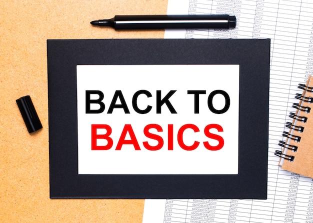 Op een houten tafel ligt een zwarte open stift, een bruin notitieblok en een vel papier in een zwarte lijst met de tekst back to basics.
