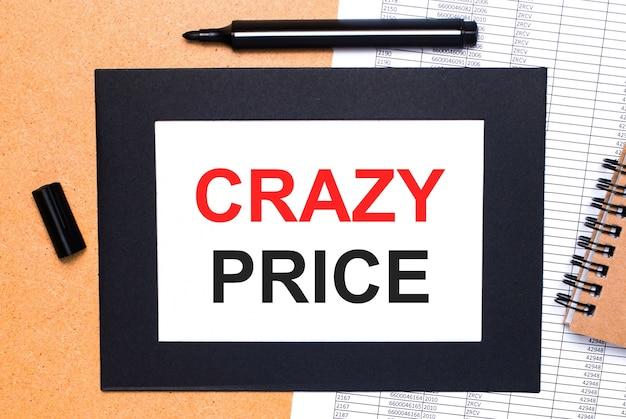 Op een houten tafel ligt een zwarte open stift, een bruin notitieblok en een vel papier in een zwarte lijst met de tekst crazy price. uitzicht van boven.