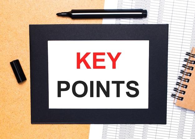 Op een houten tafel ligt een zwarte open stift, een bruin notitieblok en een vel papier in een zwarte lijst met de tekst key points. uitzicht van boven.