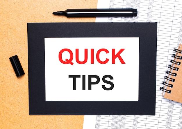 Op een houten tafel ligt een zwarte open stift, een bruin notitieblok en een vel papier in een zwarte lijst met de tekst quick tips. uitzicht van boven.