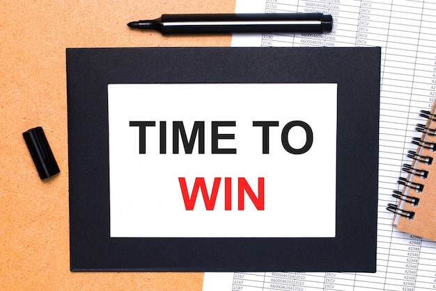Op een houten tafel ligt een zwarte open stift, een bruin notitieblok en een vel papier in een zwarte lijst met de tekst time to win. uitzicht van boven.