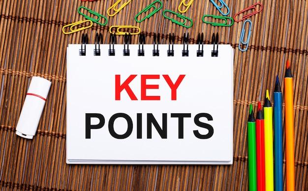 Op een houten tafel meerkleurige potloden, paperclips, een witte flashdrive en een notitieboekje met de tekst key points. plat leggen