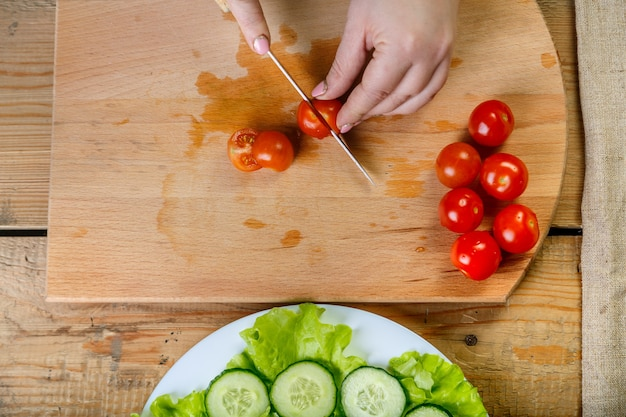 Op een houten tafel messen een vrouw een regime van tomaten voor groentesalade. bovenaanzicht