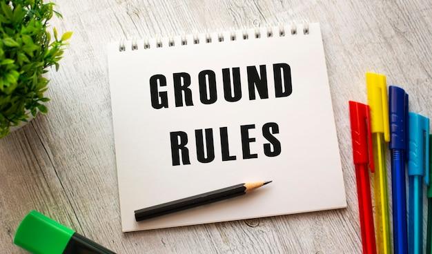 Op een houten tafel met gekleurde pennen ligt een notitieboekje op een veer met de tekst ground rules