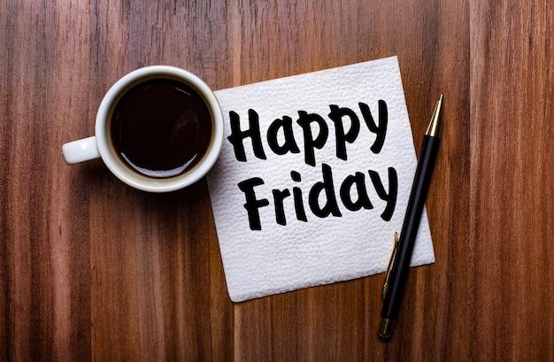 Op een houten tafel naast een witte kop koffie en een pen ligt een wit papieren servet met de woorden happy friday