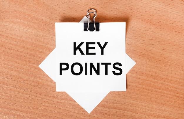 Op een houten tafel onder een zwarte paperclip ligt een vel wit papier met de tekst key points