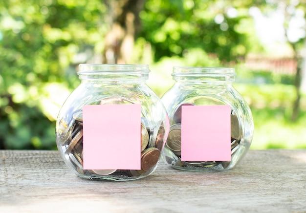 Op een houten tafel staan glazen potten met munten en bijgevoegde blanco stickers voor inscripties. investeringsbudget. financieel begrip.