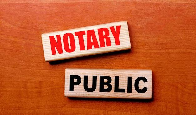 Op een houten tafel staan twee houten blokken met de tekst notary public