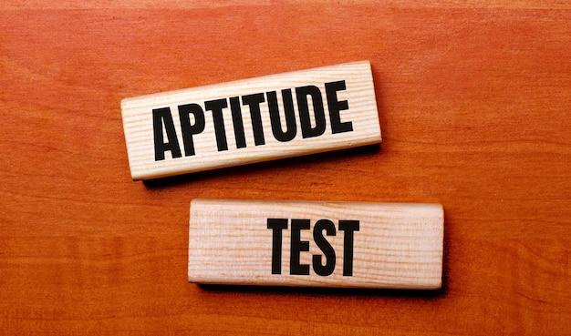 Op een houten tafel staan twee houten blokken met de tekst vraag aptitude test