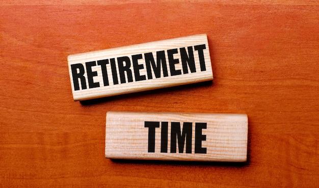 Op een houten tafel staan twee houten blokken met de tekst vraag pensioentijd