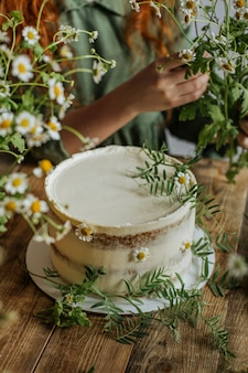 Op een houten tafel staat een taart versierd met kamillebloemen