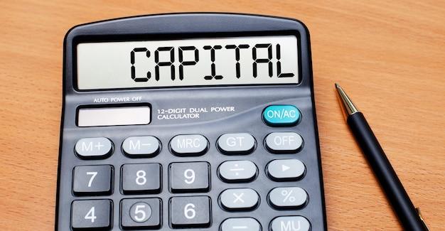 Op een houten tafel staat een zwarte pen en een rekenmachine met de tekst capital. bedrijfsconcept