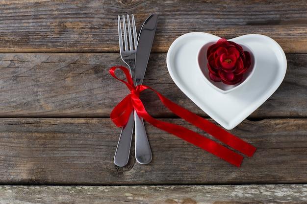 Op een houten tafel, twee hartvormige borden, een rode rozenknop en bestek vastgebonden met een rood lint
