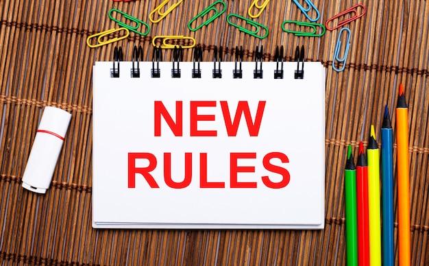 Op een houten tafel veelkleurige potloden, paperclips, een witte flashdrive en een notitieboekje met de tekst nieuwe regels. plat leggen