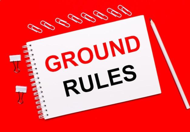 Op een knalrode achtergrond een wit potlood, witte paperclips en een wit notitieboekje met de tekst ground rules.