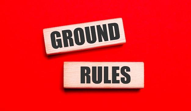 Op een knalrode achtergrond staan twee lichte houten blokken met de tekst ground rules