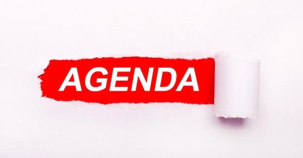 Op een knalrode achtergrond, wit papier met een gescheurde streep en het opschrift agenda.