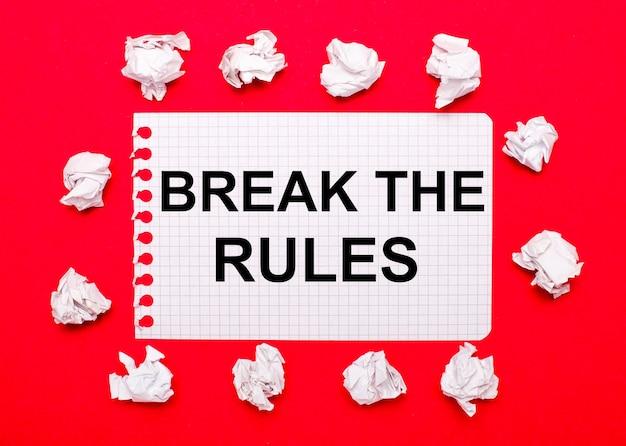 Op een knalrode achtergrond, witte verfrommelde vellen papier en een vel papier met de tekst break the rules