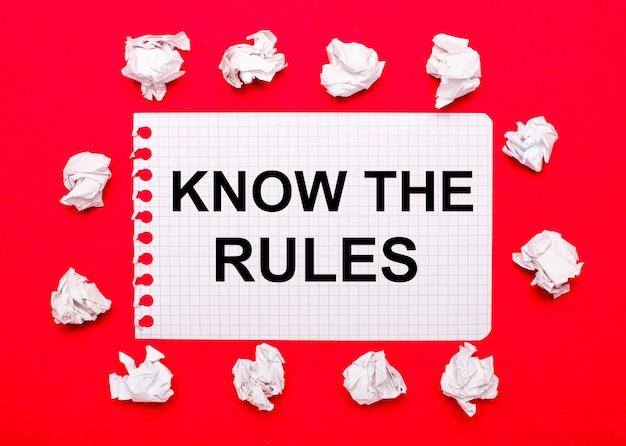 Op een knalrode achtergrond, witte verfrommelde vellen papier en een vel papier met de tekst know the rules