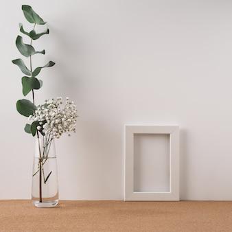 Op een kurk staan een lijst en een vaas met eucalyptus en witte bloemen