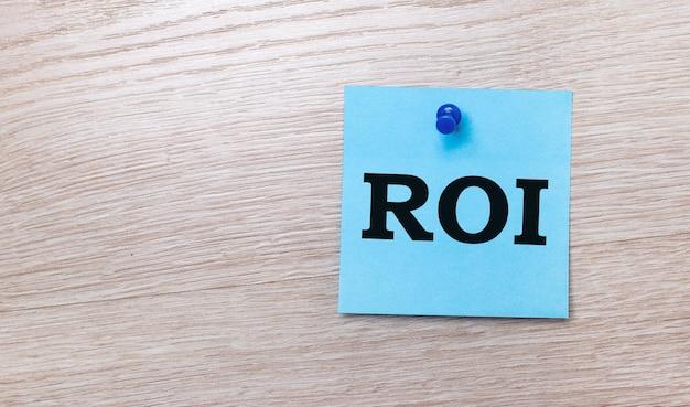 Op een licht houten achtergrond - een lichtblauwe vierkante sticker met de tekst roi return on investment