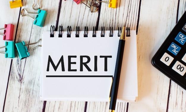 Op een licht houten tafel liggen een rekenmachine, veelkleurige paperclips en een notitieboekje met een pen en het woord merit