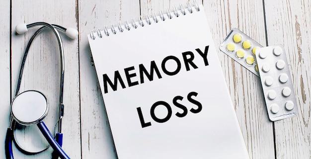 Op een licht houten tafel liggen een stethoscoop, pillen en een notitieboekje met het opschrift memory loss. medisch concept