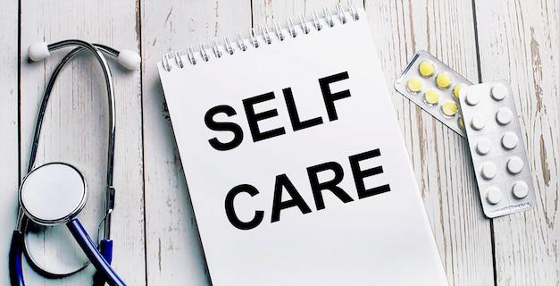 Op een licht houten tafel liggen een stethoscoop, pillen en een notitieboekje met het opschrift self care. medisch concept