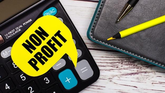 Op een licht houten tafel ligt een rekenmachine, een notitieboekje, een pen, een geel potlood en een gele kaart met de tekst non profit. bedrijfsconcept.