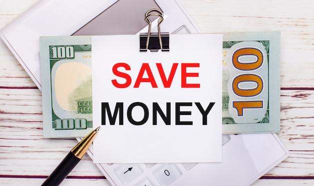 Op een licht houten tafel ligt een witte rekenmachine, een pen, biljetten en een vel papier onder een zwarte paperclip met de tekst save money. bedrijfsconcept