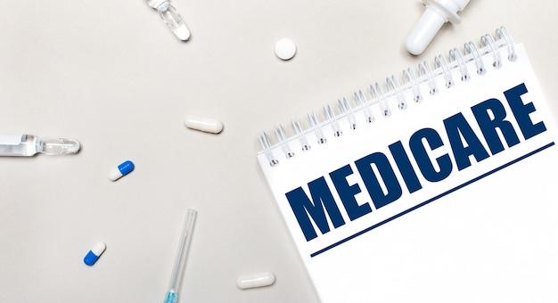 Op een licht oppervlak, een injectiespuit, een stethoscoop, medicijnflesjes, een ampul en een wit notitieblok met de tekst medicare