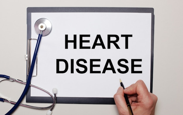 Op een licht oppervlak, een stethoscoop en een vel papier, waarop een man heart disease schrijft