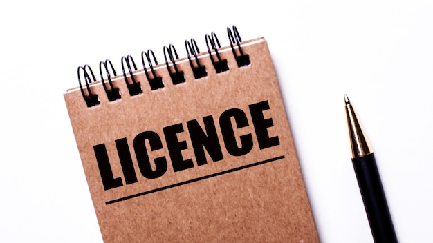 Op een licht oppervlak, een zwarte pen en een bruin notitieboekje op zwarte veren met het opschrift license