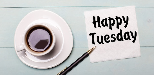 Op een lichtblauw houten dienblad staat een witte kop koffie, een handvat en een servet met de tekst gelukkige dinsdag.