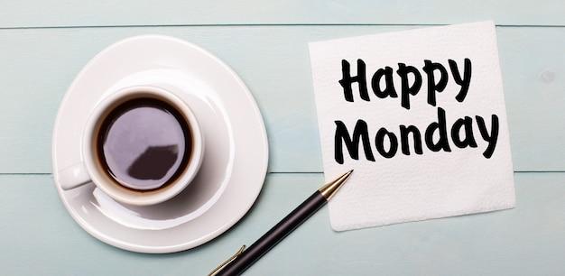 Op een lichtblauw houten dienblad staat een witte kop koffie, een handvat en een servet met de tekst happy monday.