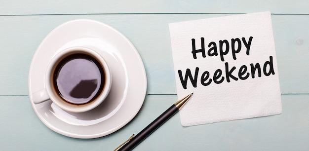 Op een lichtblauw houten dienblad staat een witte kop koffie, een handvat en een servet met de tekst happy weekend