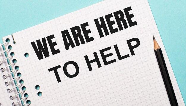 Op een lichtblauwe achtergrond een geruit notitieboekje met de woorden we are here to help en een zwart potlood.