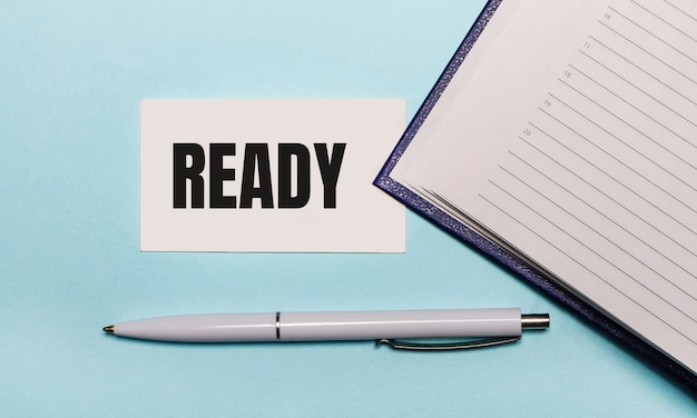 Op een lichtblauwe achtergrond een opengeslagen notitieboekje, een witte pen en een kaartje met de tekst ready. uitzicht van boven