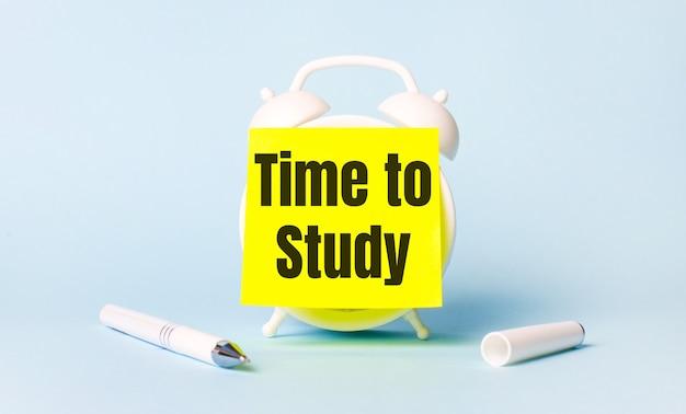 Op een lichtblauwe achtergrond - een wit handvat en een wekker met daarop een knalgele sticker gelijmd met de tekst time to study
