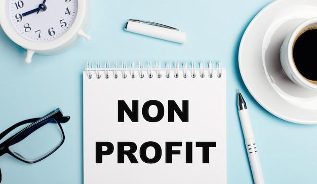 Op een lichtblauwe achtergrond een witte kop koffie, een witte wekker, een witte pen en een notitieboekje met de tekst non profit. uitzicht van boven