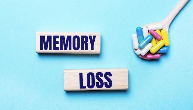 Op een lichtblauwe achtergrond, heldere veelkleurige pillen in een lepel en twee houten blokken met de tekst memory loss. medisch concept