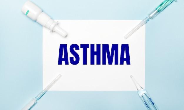 Op een lichtblauwe achtergrond, injectiespuiten, een medicijnflesje, een ampul en een wit vel papier met de tekst asthma. medisch concept.