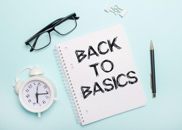Op een lichtblauwe achtergrond liggen een zwarte bril en een pen, een witte wekker, witte paperclips en een notitieboekje met de woorden back to basics. bedrijfsconcept