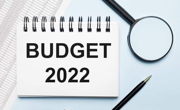 Op een lichtblauwe achtergrond, rapporten, een vergrootglas, een pen en een notitieboekje met de tekst budget 2022. bedrijfsconcept. plat leggen.