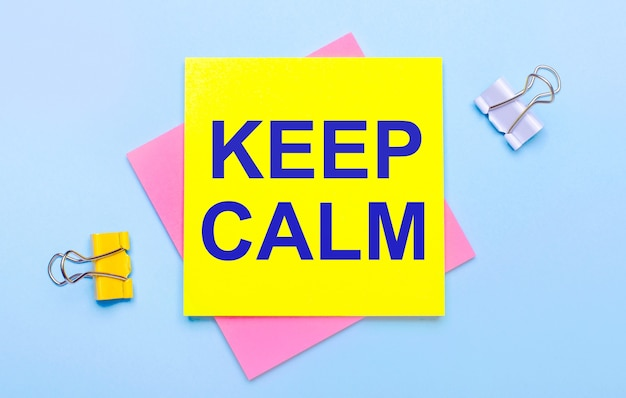 Op een lichtblauwe achtergrond staan gele en witte paperclips, roze en gele plaknotities met de tekst keep calm