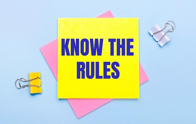 Op een lichtblauwe achtergrond staan gele en witte paperclips, roze en gele plaknotities met de tekst know the rules