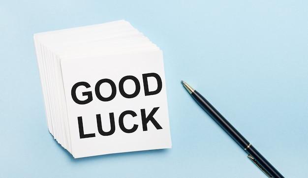 Op een lichtblauwe achtergrond staat een zwarte pen en een stapel wit briefpapier met de tekst good luck